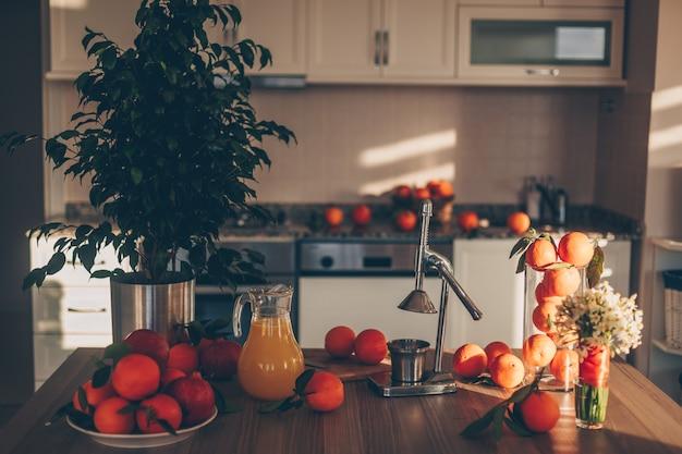 Einige früchte mit saftpresse und baum auf tisch und küche, seitenansicht.