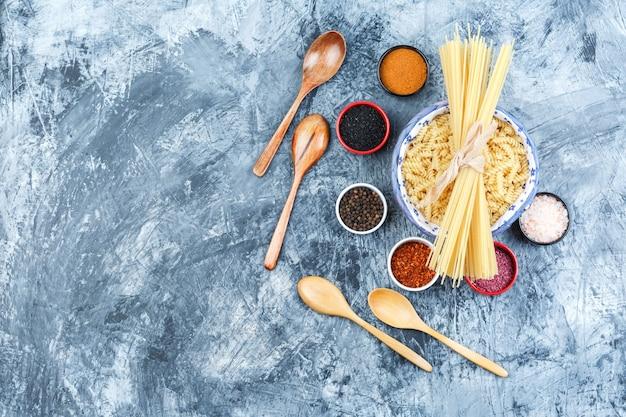 Einige fusilli-nudeln mit spaghetti, gewürzen, holzlöffeln in einer schüssel auf grauem gipshintergrund, draufsicht.