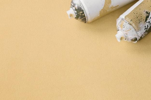 Einige gebrauchte orangefarbene sprühdosen mit farbtropfen liegen auf einer decke aus weichem und pelzigem hellorangenem vliesstoff.