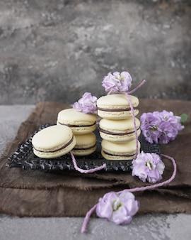 Einige gelbe macarons auf grauem hintergrund, verziert mit blumen. französisches gebäck