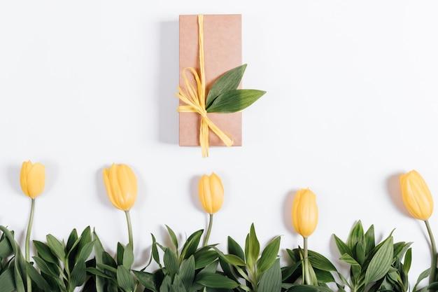 Einige gelbe tulpen und geschenkbox mit einem bogen auf einem weißen hintergrund