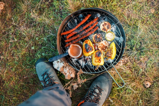 Einige gemüsewürste und eine türkische kaffeekanne auf dem grill stehen zum verzehr bereit