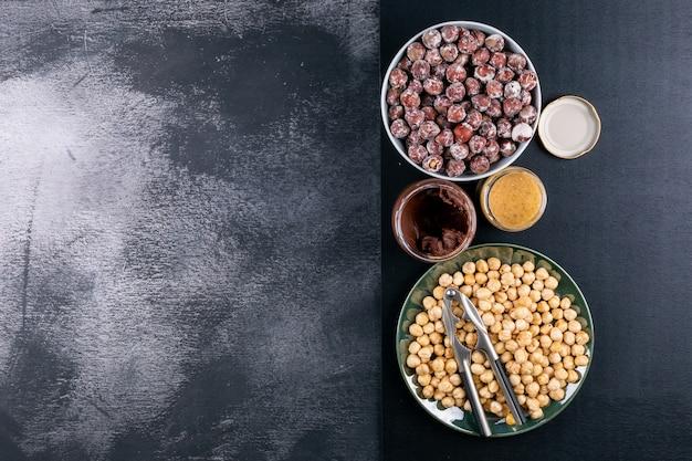 Einige geschälte und gereinigte haselnüsse mit kakaoaufstrich und nussknacker in einer weißen schüssel auf dunklem steintisch, draufsicht.