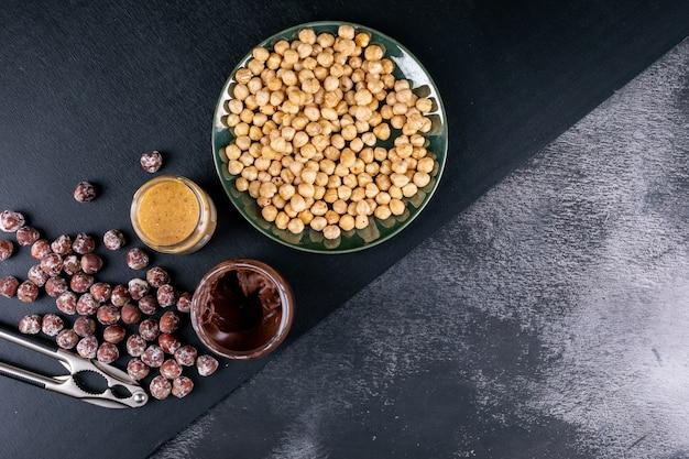 Einige geschälte und gereinigte haselnüsse mit kakaostreifen und nussknacker in einem glasigen teller auf dunklem steintisch, draufsicht.