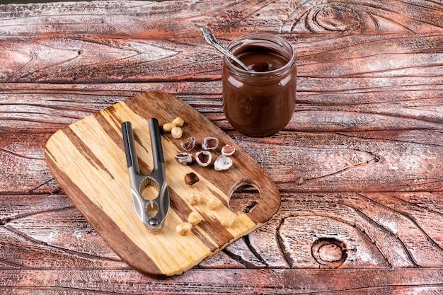 Einige geschälte und gereinigte haselnüsse mit kakaostreifen und nussknackern auf holztisch, draufsicht.