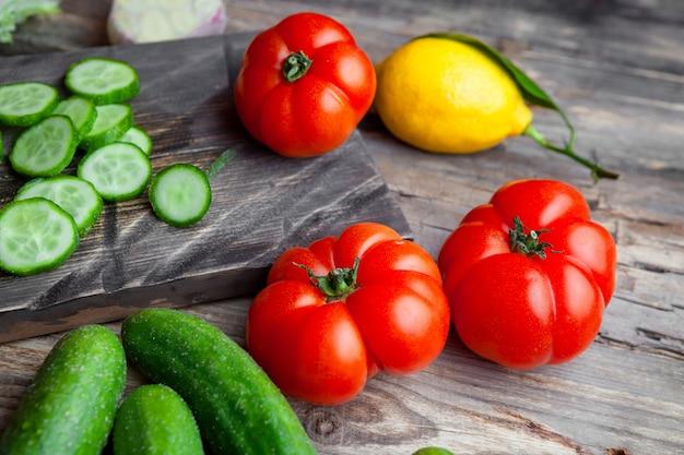 Einige geschnittene gurke mit knoblauch, tomaten, zitrone in einem schneidebrett auf dunklem hölzernem hintergrund, hohe winkelansicht