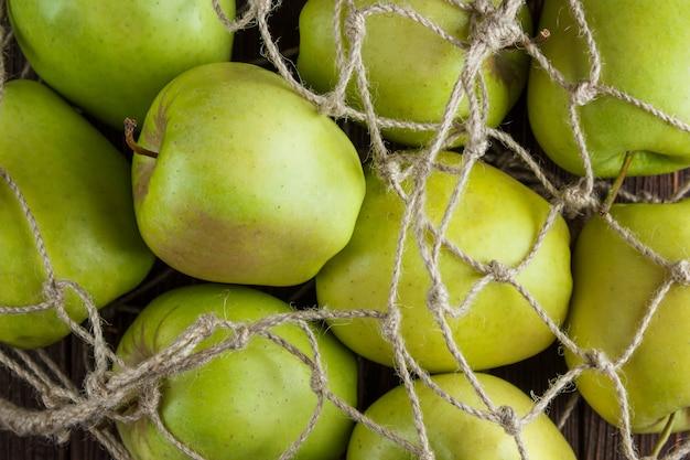 Einige grüne äpfel in einem netzbeutel auf hölzernem hintergrund, draufsicht.