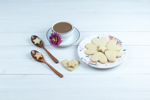 Einige herzförmige und sternförmige kekse mit blumen, kekse in holzlöffeln, tasse kaffee in einer weißen platte auf weißem holzbretthintergrund, hohe winkelansicht.
