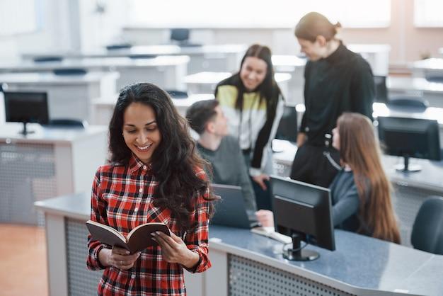 Einige interessante informationen. gruppe junger leute in freizeitkleidung, die im modernen büro arbeiten