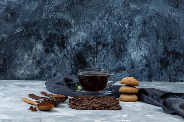 Einige kaffeebohnen, eine tasse kaffee mit kaffeebohnen, instantkaffee, kaffeemehl in holzlöffeln