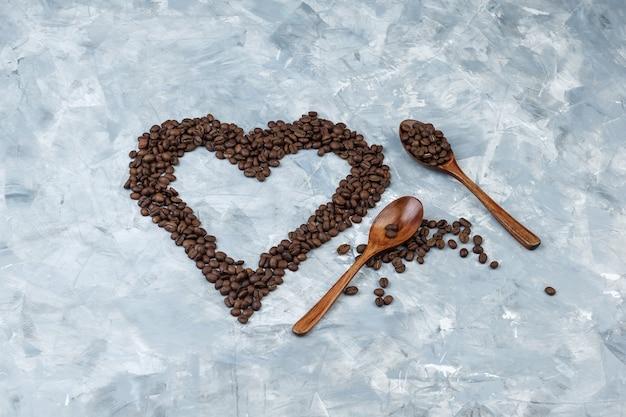 Einige kaffeebohnen in holzlöffeln auf grauem gipshintergrund, flach liegen.