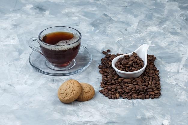 Einige kaffeebohnen mit keksen, tasse kaffee in einem weißen porzellankrug auf blauem marmorhintergrund, nahaufnahme.