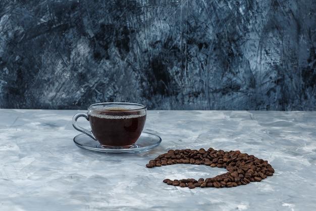 Einige kaffeebohnen mit tasse kaffee auf dunkel- und hellblauem marmorhintergrund, nahaufnahme.