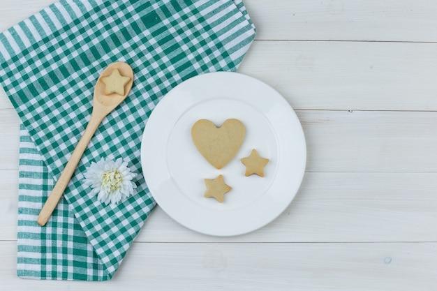 Einige kekse mit blume im teller und holzlöffel auf holz- und küchentuchhintergrund, flach liegen.