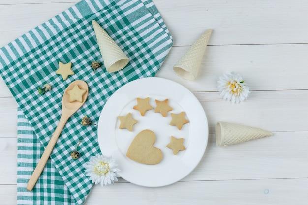 Einige kekse mit waffeltüten, blumen im teller und holzlöffel auf holz- und küchentuchhintergrund, flach liegen.