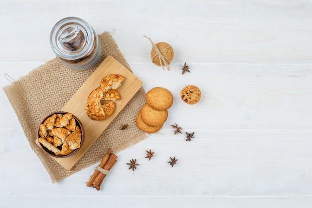 Einige kekse mit zimt und nelken auf einem stück sack auf weißer oberfläche