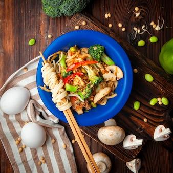 Einige köstliche mahlzeit mit eiern und pilzen in einem blauen teller auf holz, stoff und dunklem hölzernem hintergrund, draufsicht.