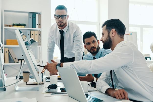 Einige konzepte durcharbeiten. gruppe junger moderner männer in formeller kleidung, die mit computern arbeiten, während sie im büro sitzen