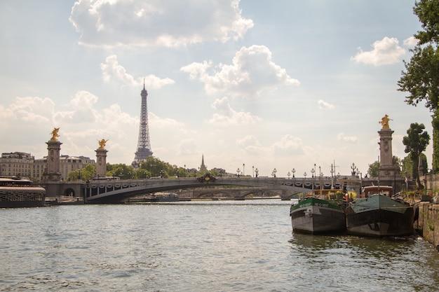 Einige lastkähne und alexander die dritte brücke auf dem hintergrund des eiffelturms in paris