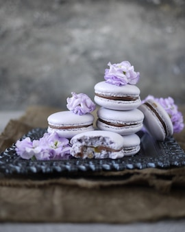 Einige lavendel macarons auf grauem hintergrund, dekoriert mit blumen. französisches gebäck
