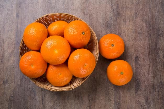 Einige mandarinen in einem korb über einer holzoberfläche. frische früchte