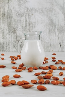 Einige milchkaraffe mit mandeln auf weißem hölzernem hintergrund, seitenansicht.