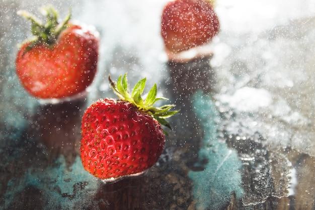 Einige reife frische erdbeeren aus eigenem anbau auf der hellblauen oberfläche mit gefrierendem sprühwasser tropfen