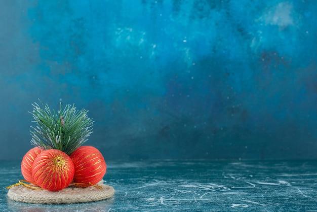 Einige rote festliche weihnachtsspielzeuge auf marmor.