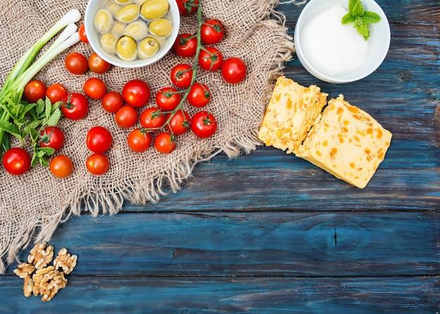 Einige rote frische kirschen, frühlingszwiebeln, koriander, käse, knoblauch, oliven in der schüssel, brot auf dunklem rustikalem holzhintergrund