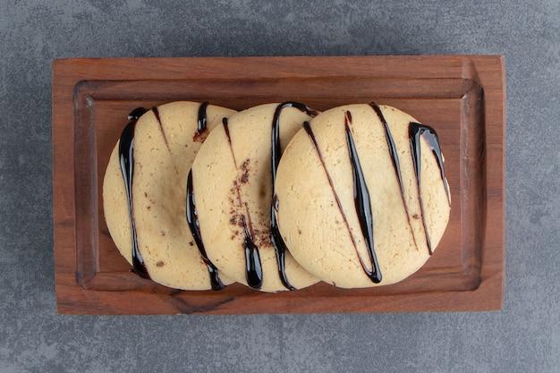 Einige runde kekse mit schokolade auf einem holzbrett