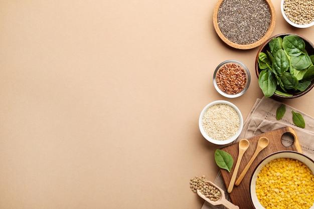 Einige schalen mit gesundem veganem superfood-müsli und spinat auf beigem hintergrund. nahansicht