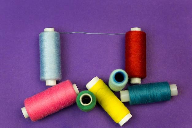 Einige spulen mit threads auf einem blauen hintergrund.