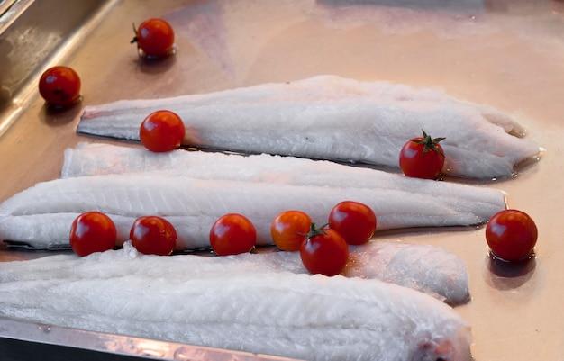 Einige stücke roher kabeljau und tomaten