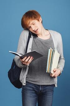 Einige tage vor der prüfung. studienkonzept. junger attraktiver rothaariger student in grauer kleidung mit schwarzem rucksack, der viele bücher hält und mit freund über das universitätsleben telefoniert.