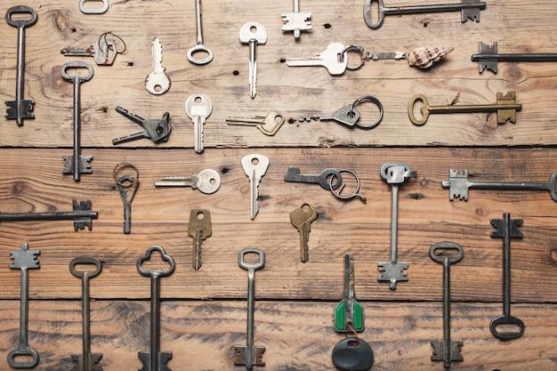 Einige türschlüssel ausgerichtet auf alter holzoberfläche, sicherheitskonzept hintergrund.