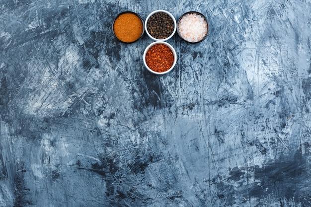 Einige verschiedene gewürze in kleinen schalen auf grauem gipshintergrund, draufsicht.
