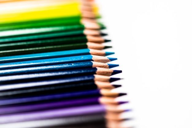 Einige verschiedenfarbige hölzerne bleistiftstifte, die in einer reihe vor einem weißen isolierten hintergrund platziert werden