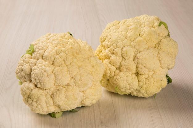 Einige weiße blumenkohlblumen über einer holzoberfläche von oben gesehen. frisches gemüse.