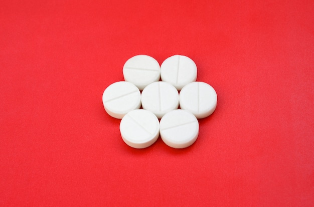 Einige weiße tabletten liegen auf einer hellen roten hintergrundoberfläche