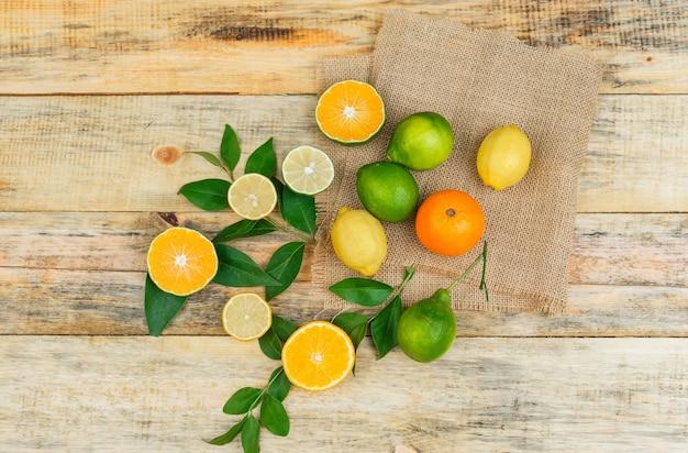 Einige zitrusfrüchte mit blättern auf einem leinen-tischset auf holzbrett