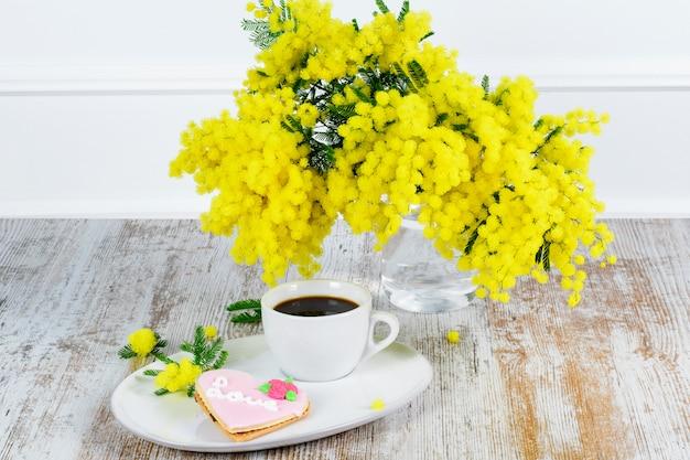 Einige zweige mimosen, eine tasse kaffee und ein kuchen in form eines herzens auf dem weißen teller. sant valentinstag konzept