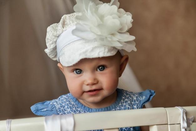 Einjähriges blauäugiges kind in stilvollem hutblick in die kamera von der krippe. kleines und süßes baby mit lächeln, das im kinderzimmer sitzt und mutter wartet. konzept der richtigen erziehung und kindheit