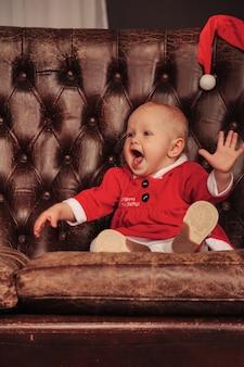 Einjähriges kind mit blauen augen im weihnachtskostüm auf sessel im wohnzimmer. babygefühl am feiertagsabend des antiken stuhls. konzept der familienfeier von weihnachten und happy new year