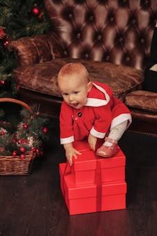 Einjähriges kind mit blauen augen im weihnachtskostüm, das im wohnzimmer mit baum und geschenkboxen spielt. nettes baby mit emotionsfeiertagsabend. konzept der familienfeier von weihnachten und happy new year