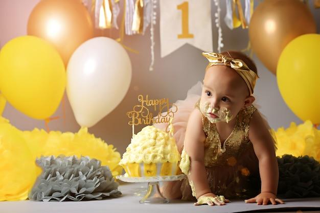 Einjähriges mädchen des kleinen babygeburtstages, das ihren gelben kuchen zerquetscht