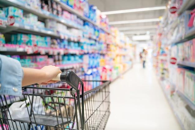 Einkauf in einem supermarkt. schließen sie oben von einer frau, die in einem supermarkt kauft. kunde, der einen warenkorb in einem supermarkt drückt.