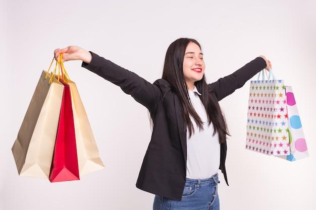Einkaufen, emotionen, menschenkonzept. junge glückliche asiatische frau mit bunten papiertüten nach dem einkaufen