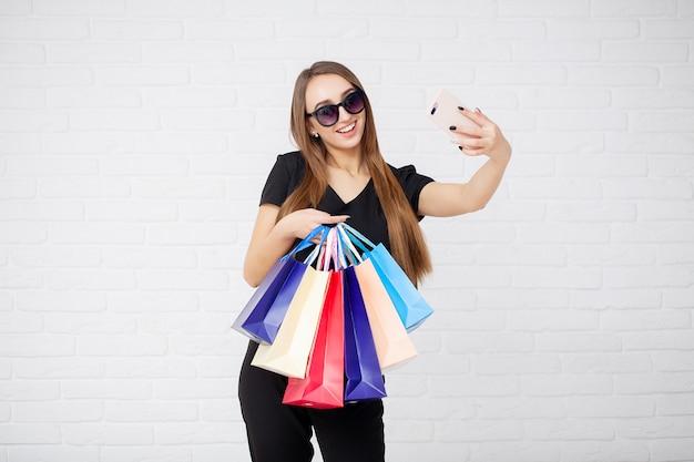 Einkaufen. frau, die farbige taschen auf hellem hintergrund in schwarzem freitag-feiertag hält