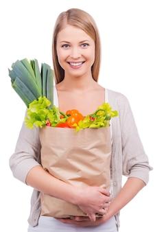 Einkaufen für gute küche. schöne junge frau, die eine einkaufstasche voller lebensmittel trägt und in die kamera schaut, während sie vor weißem hintergrund steht