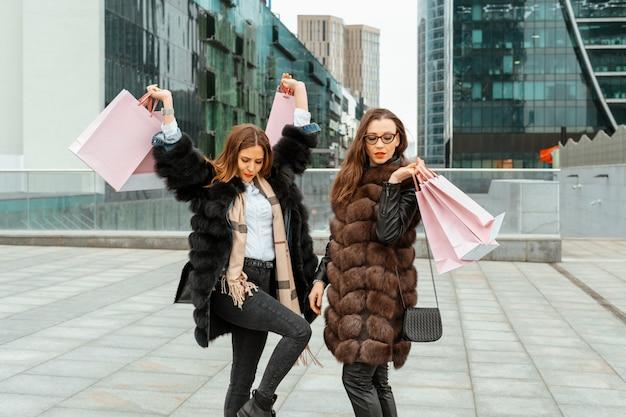 Einkaufen, konsum. bürozentrum, glasgebäude. zwei schöne mädchen gehen mit papiertüten aus geschäften auf der straße. einkaufen im viertel der wolkenkratzer. unterhaltung moderner frauen.
